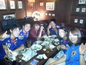 Shun à droite accompagnés de ses amis dans un pub de Tokyo